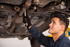Fixing a car at an auto shop. Young mechanic using a wrench and fixing a suspended car at an auto shop Stock Photos