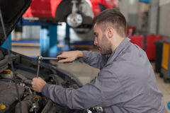 Fixing Car Engine with Ratchet Wrench Royalty Free Stock Photos