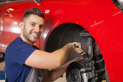 Fixing a Car Suspension. Smiling mechanic repairing a car suspension in auto mechanic shop royalty free stock images