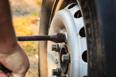 Fixing car tire with rim socket wrench Royalty Free Stock Photo