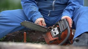 Fixing chainsaw in slow motion. Chainsaw broken while cutting, person unscrew chain and repair it stock video footage