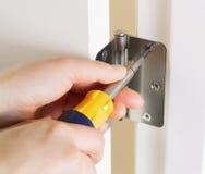 Fixing Door Hinge. Photo of female hands, with screwdriver, tightening door hinge royalty free stock photo