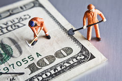 Fixing the economy. Worker figurines placed on a 100 dollar bill Stock Photography