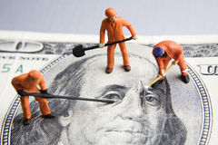 Fixing the economy. Worker figurines placed on a 100 dollar bill Stock Photo