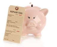 Fixing financial problems. Repair tag hanging on pink piggy bank with reflection on white background Royalty Free Stock Photo