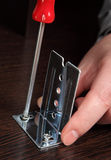 Fixing furniture fittings, screwing screws using a hand screwdr royalty free stock photo
