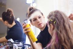 Fixing hairdo with hairspray royalty free stock photos