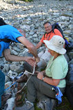Fixing Hiking Boot. Backpackers repairing a hiking boot on a rockfall. British Columbia. Canada Stock Photos
