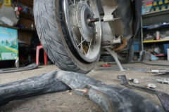 Fixing motorbike rear wheel. In Thailand service center Royalty Free Stock Photos