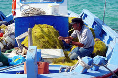 Fixing the net. A greek fisherman is fixing his net on his boat at samos island in greece royalty free stock images