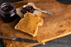 Peanut Butter and Jelly Sandwich on a Wooden Kitchen Counter. Fixing a Peanut Butter and Jelly Sandwich on a Wooden Kitchen Counter stock photo