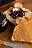 Peanut Butter and Jelly Sandwich on a Wooden Kitchen Counter. Fixing a Peanut Butter and Jelly Sandwich on a Wooden Kitchen Counter royalty free stock image