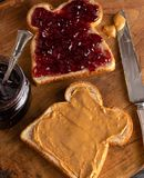 Peanut Butter and Jelly Sandwich on a Wooden Kitchen Counter. Fixing a Peanut Butter and Jelly Sandwich on a Wooden Kitchen Counter royalty free stock images