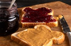 Peanut Butter and Jelly Sandwich on a Wooden Kitchen Counter. Fixing a Peanut Butter and Jelly Sandwich on a Wooden Kitchen Counter stock photos