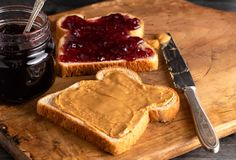 Peanut Butter and Jelly Sandwich on a Wooden Kitchen Counter. Fixing a Peanut Butter and Jelly Sandwich on a Wooden Kitchen Counter royalty free stock photo
