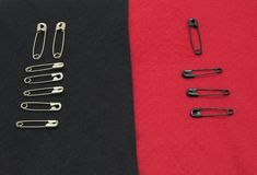 Fixing pins on black and red felt Stock Image