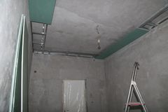 Fixing plaster boards at the ceiling during construction. Fixing plaster boards at the ceiling of a house under construction royalty free stock photo