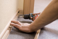 Fixing plinth in the room. Man is fixing plinth in the room royalty free stock images