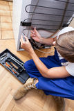 Fixing a refrigerator. A repairman sitting on the floor fixing a fridge with special tools Royalty Free Stock Image