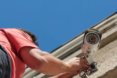 Fixing the security camera. Electrical Worker splicing wires on security camera Royalty Free Stock Photos