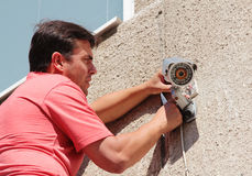 Fixing the security camera. Electrical Worker splicing wires on security camera Royalty Free Stock Photography