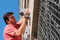 Fixing the security camera. Electrical Worker splicing wires on security camera Stock Photography