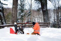 Fixing a snow blower. Man outdoors in the snow fixing a snow blower royalty free stock photography