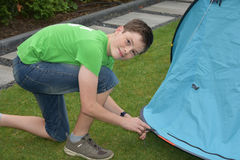 Fixing the tent. Teenage boy puts  in tent pegs. Fixing the tent on the ground Stock Photo