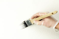 Fixing to Sell. Home touch up painting off-white paint on wall with one and a half inch brush by vinyl gloved hand Royalty Free Stock Photo