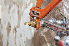 Fixing valve tap with leaking water using red plumber pliers. Stock Image