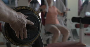 Fixing weight plate on the bar-bell. Close-up shot of man fixing extra weight disk on the bar-bell, woman training on exercise machine in background stock video footage