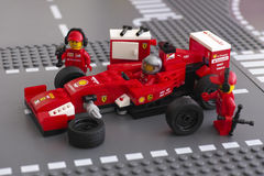 Fixing wheel of Ferrari F14 T race car by Lego Speed Champions Royalty Free Stock Image