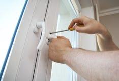 Fixing window handle. Professional handyman fixing window handle at home stock images