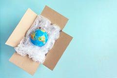 Fizyczna kula ziemska, ziemia w plastikowym opakunku w kartonu pudełku na błękita plecy obraz stock