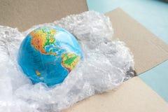 Fizyczna kula ziemska, ziemia w plastikowym opakunku w kartonu pudełku na błękita plecy zdjęcia stock