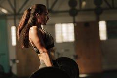 Fizycznie dysponowana kobieta podnosi ciężkich ciężary Zdjęcie Stock