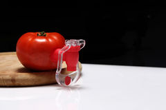 Fizz keeper. Red tomato and a fizz keeper on a wooden trencher royalty free stock photos