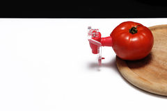 Fizz keeper. Red tomato and a fizz keeper on a wooden trencher royalty free stock photography
