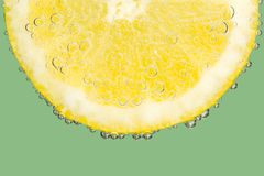 Fizzy Lemon Slice with Bubbles on Cool Green Stock Photos