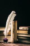 Fjäder på mörk bakgrund mot gammala böcker Gammal bläckhorn med den near snirkeln och böcker för fjäder på svart bakgrund Royaltyfri Foto