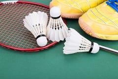 Fjäderboll för badminton tre med racket och skor på den gröna domstolen Arkivbilder