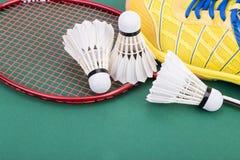 Fjäderboll för badminton tre med racket och skor på den gröna domstolen Arkivfoton