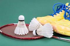 Fjäderboll för badminton tre med racket och skor på den gröna domstolen Royaltyfria Foton