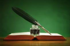 Fjäderpenna och bläckhorn på den gamla boken Royaltyfri Foto