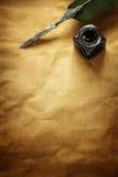 Fjäderpenna och färgpulver väl på pergamentpapper Royaltyfri Foto