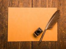 Fjäderpenna och färgpulver väl på träskrivbordet arkivbilder