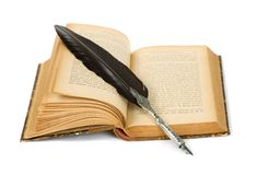 Fjäderpenna som vilar på en gammal bok royaltyfri bild