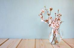 Fjädra buketten av blommor på trätabellen med mintkaramellbakgrund tappning filtrerad bild royaltyfria foton