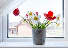 Fjädra buketten av röda tulpan och påskliljor i en vas på fönstret Fotografering för Bildbyråer