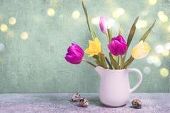 Fjädra buketten av tulpan och påskliljor i en vit vas tillgänglig hälsning för korteaster eps mapp Arkivbilder